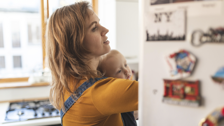 Woman in the kitchen opening the fridge and holding her son